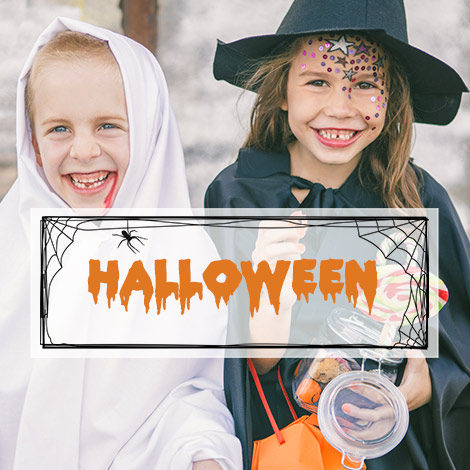Two girls in fancy dress with halloween text