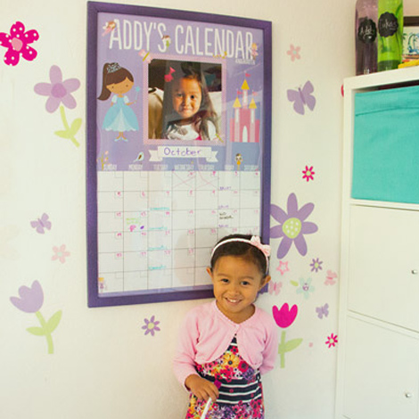 A girl with dry-erase poster calendar on the wall